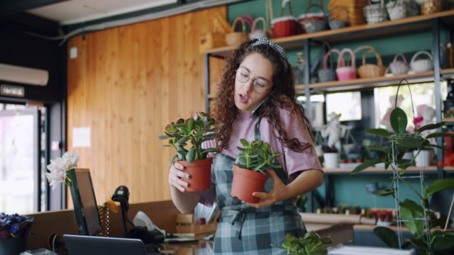 slow motion of young florist taking order on mobile phone talking holding plants - owner laptop smartphone video stock e b–roll