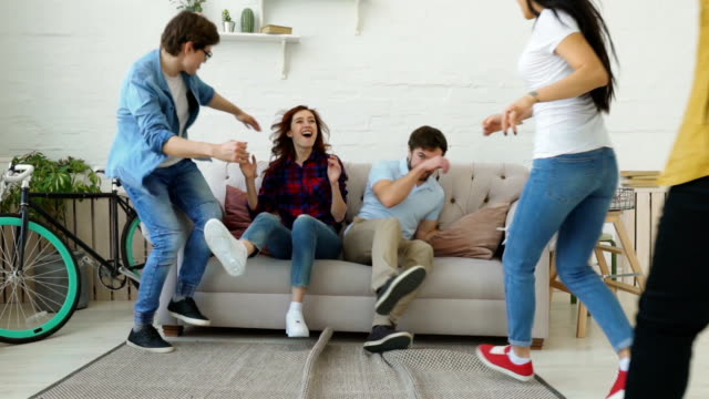 slow motion of young friends running and jumping on sofa then smiling and showing thumbs up all together at home - student life stock videos & royalty-free footage