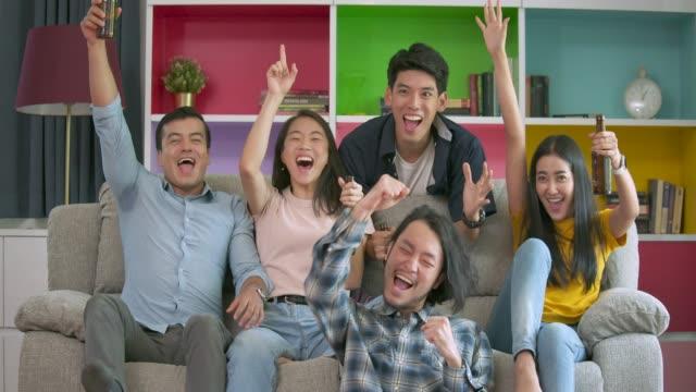 若いお友達の家で一緒にテレビでフットボールの試合を見て、ゴールを祝ってのスローモーション。 - 応援点の映像素材/bロール