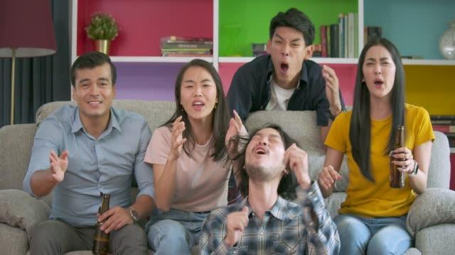 若いお友達の家で一緒にテレビでフットボールの試合を見て、自分の好きなチームの一致を失うについて失望のスローモーション。 - 応援点の映像素材/bロール