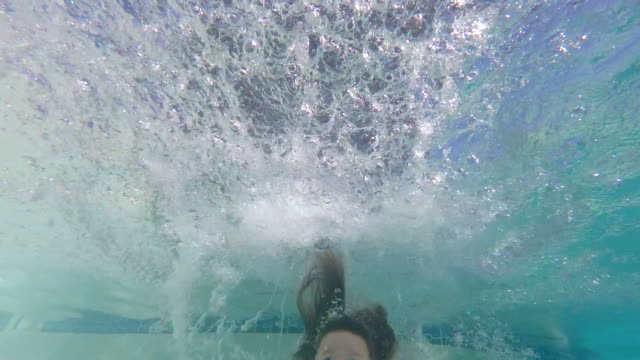 Slow motion of young girl jumping in pool and smiling at camera video
