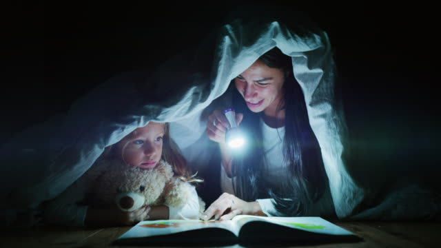 Slow motion of young mother is reading a goodnight story to her little daughter in the dark illuminating with a torch under the blanket.