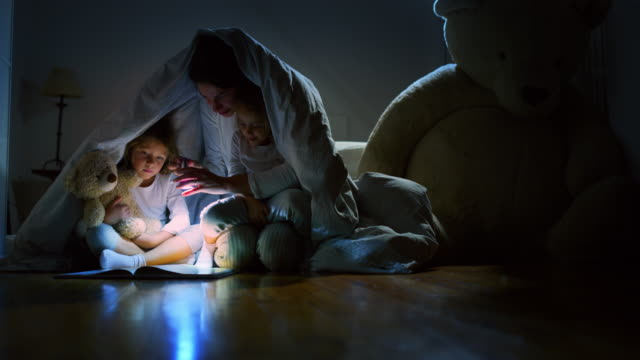 Slow motion of young mother is reading a goodnight story to her little daughters in the dark illuminating with a torch under the blanket. Slow motion of young mother is reading a goodnight story to her little daughters in the dark illuminating with a torch under the blanket. Concept of family, childhood, love, health, education blanket stock videos & royalty-free footage