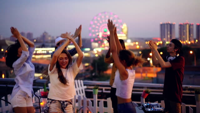 ダンスのプロのディスク ジョッキーと高さの屋上パーティーで手をたたく若い人々 のスローモーション。男性と女性は楽しい時を過すし、週末でリラックスします。 - 屋根点の映像素材/bロール