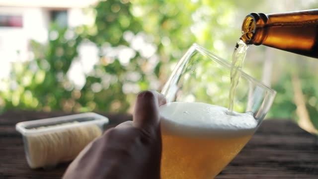 뒤뜰에서 유리에 병에서 맥주를 붓는 젊은 사람의 슬로우 모션. pov 샷 - beer 스톡 비디오 및 b-롤 화면