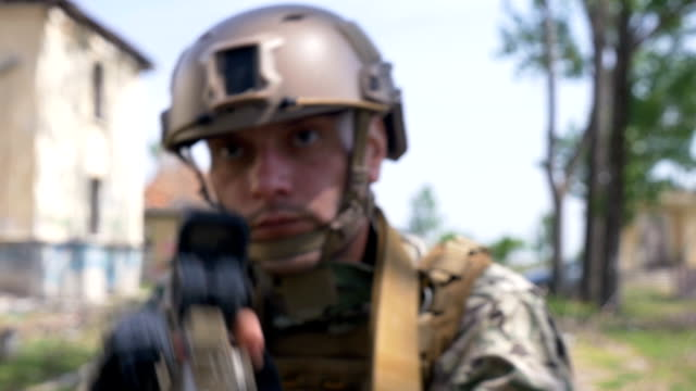 Slow motion of young soldier in an armor and helmet setting in position aiming target preparing to fire video