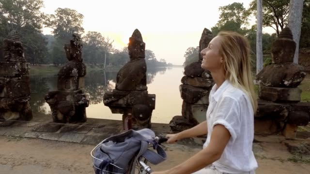 Slow motion of young woman cycling in Cambodia on ancient bridge in the Angkor Wat old temples complex