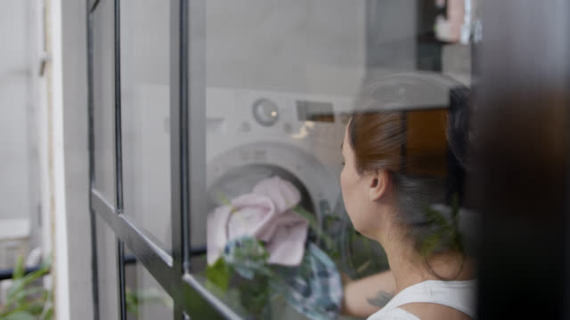 Slow motion of young woman doing the laundry at home Slow motion of young woman doing the laundry at home - Shot taken through glass window laundry basket stock videos & royalty-free footage