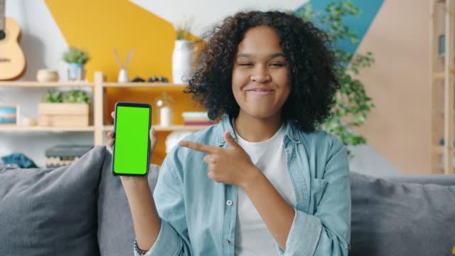 stockvideo's en b-roll-footage met langzame motie van jonge vrouw die smartphone houdt die bij scherm thuis richt - hand pointing