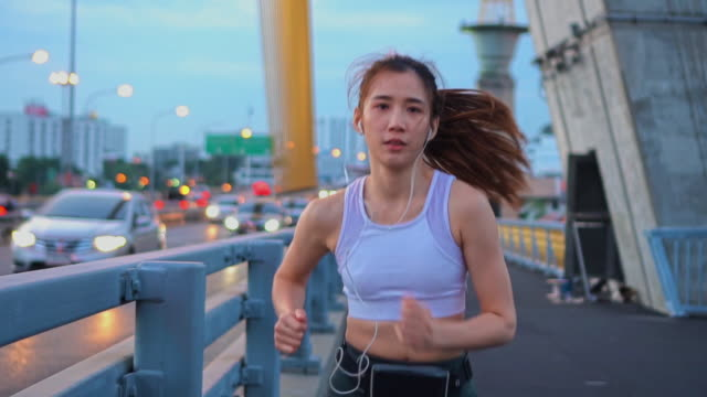 Slow motion of Young woman jogging across the bridge,Twilight