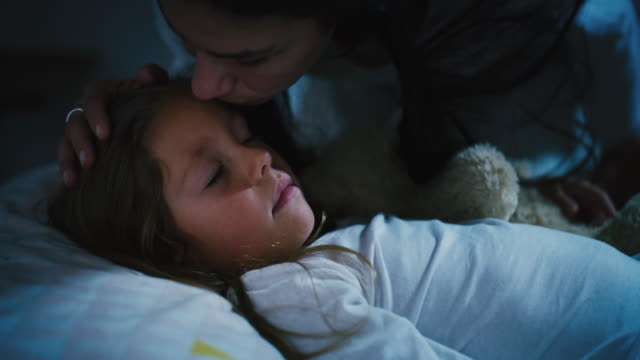 Slow motion of young woman mother giving a goodnight kiss to her little daughther while she is sleeping in the bed with the teddy bear.