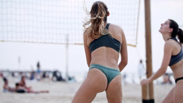 Slow motion of young women playing beach volleyball during sunset Slow motion of young women playing beach volleyball during sunset beach volleyball stock videos & royalty-free footage