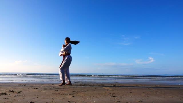 若い女性のビーチの屋外 Practising 武道のスローモーション。 ビデオ