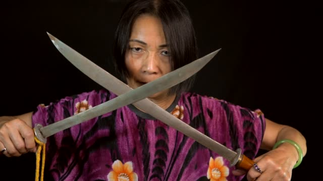 slow motion old intimidating asian woman crosses swords with black background This slow motion video shows a fierce old intimidating asian woman crossing swords with a black background. ninja stock videos & royalty-free footage