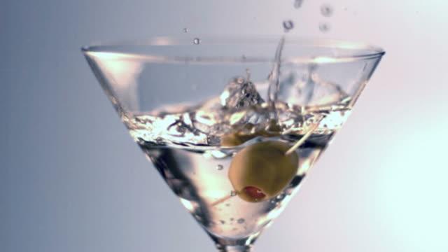 rallentatore spruzzi di verde oliva - martini video stock e b–roll