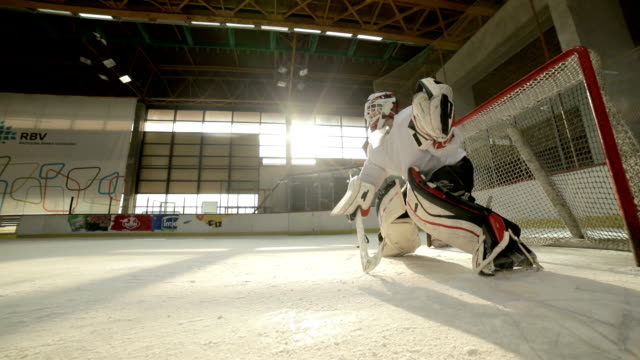 Slow motion on ice hockey goalie trying to defend his goal while one of the players is taking a shot and scoring. video