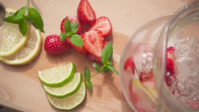 slow motion on the board slices of strawberries and lime and water is poured into the decanter - decanter video stock e b–roll