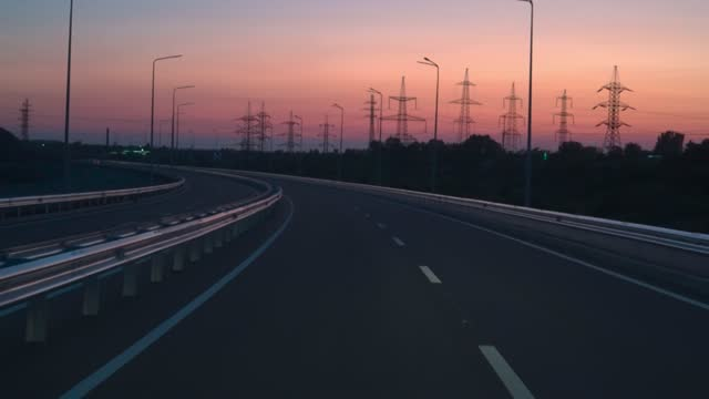 Slow motion on the freeway towards the setting sun. Power lines along the road.