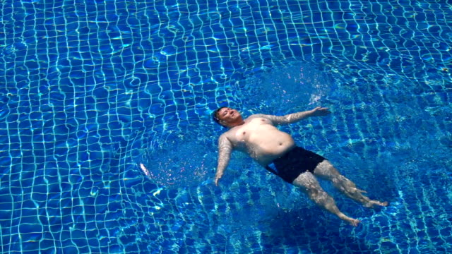 SLO MO - Fat Man Swimming Starfish Float in Swimming Pool Slow Motion - Overweight Man Swimming Starfish Float in Swimming Pool levitation stock videos & royalty-free footage