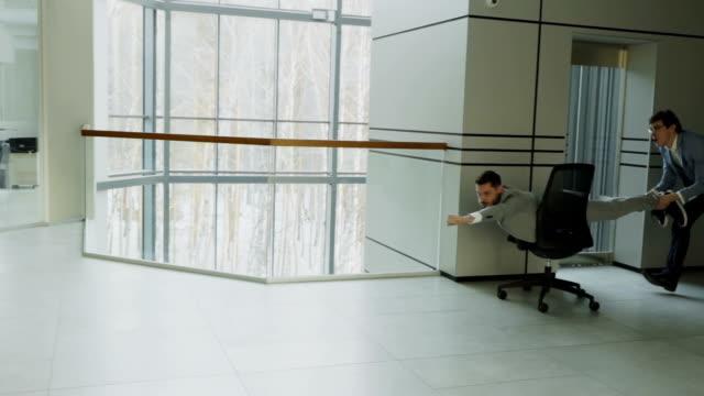 vídeos de stock, filmes e b-roll de tiro de pan câmera lenta de dois empresários engraçados andar de cadeira de escritório enquanto se diverte no átrio do centro de negócios moderno - festa da empresa