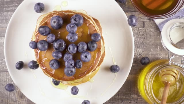 Slow motion pancakes for breakfast with berries and honey top view