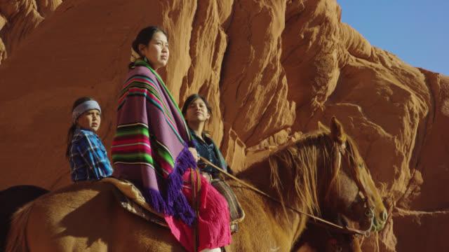 slow motion panorering shot av flera unga indianska (navajo) barn bär traditionella navajo kläder och sitter på sina hästar och tittar ut på landskapet i monument valley desert i arizona / utah bredvid en stor klippformation på en - tradition bildbanksvideor och videomaterial från bakom kulisserna