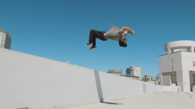 slow motion parkour athlete doing extreme backflip off wall in urban city outside isolated in sky - termine sportivo video stock e b–roll