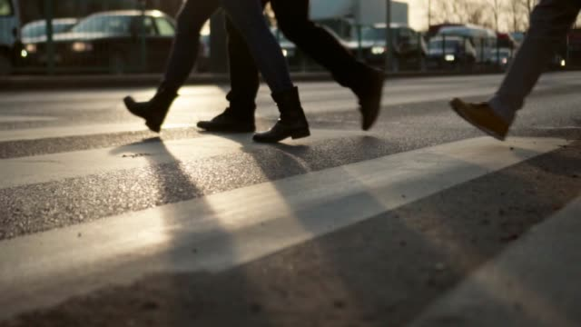 slow motion: pedestrian crosswalk at sunset - business people stock videos and b-roll footage