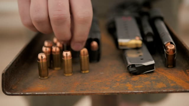 Slow Motion Person Puts Bullet Down Next to Other Ammo video
