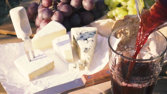 Slow motion picnic outdoors in vineyards Slow motion cheese grapes and bread near a glass in which to pour homemade red wine from a decanter cheese stock videos & royalty-free footage