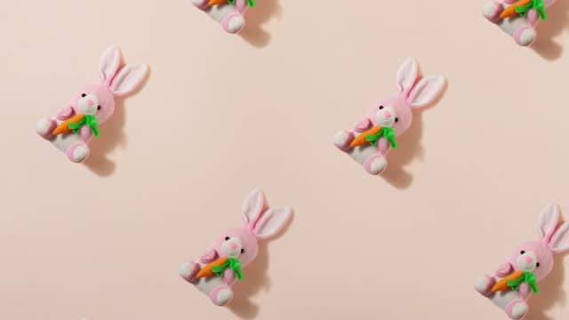 slow motion. pink plush little Easter bunny with a red carrot on a pastel beige background, toy rabbit as a pattern. Easter holiday concept. Easter background