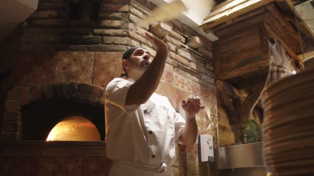 vídeos de stock e filmes b-roll de slow motion - pizza master tossing the pizza dough in the air - pizza