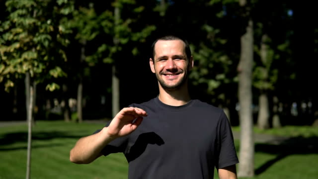 Slow motion portrait of a young guy who smiles broadly and waves his hand while walking in the park. A young attractive guy waves his hand in greeting and smiles broadly while looking into the camera.