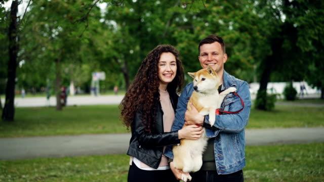 slow motion porträtt av bedårande par och renrasiga hund står tillsammans i parken, titta på kameran och leende. natur och familj koncept. - hunddjur bildbanksvideor och videomaterial från bakom kulisserna