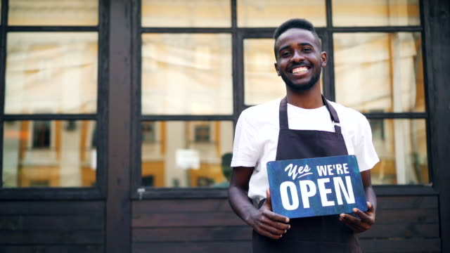 Slow motion portrait of African American guy urban cafe owner posing with we are open sign standing outdoors and looking at camera. Local business and millennials concept. Slow motion portrait of handsome African American guy urban cafe owner posing with we are open sign standing outdoors and looking at camera. Local business and millennials concept. owner stock videos & royalty-free footage
