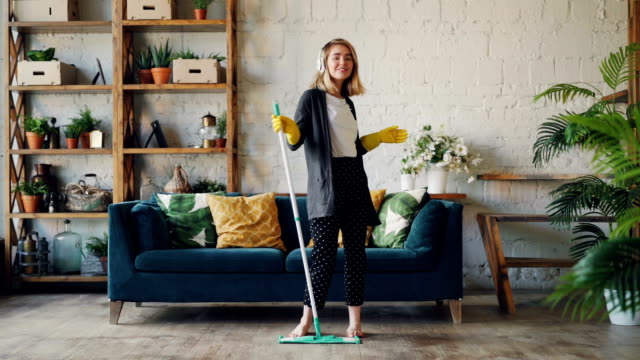 slow motion portrait of attractive blond girl listening to music with headphones, dancing with plastic flat mop and looking at camera. housework and fun concept. - radio video stock e b–roll