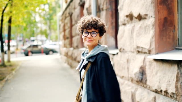 Slow motion portrait of attractive brunette walking in the street with her back to the camera then turning, smiling and looking at camera. City and leisure concept.