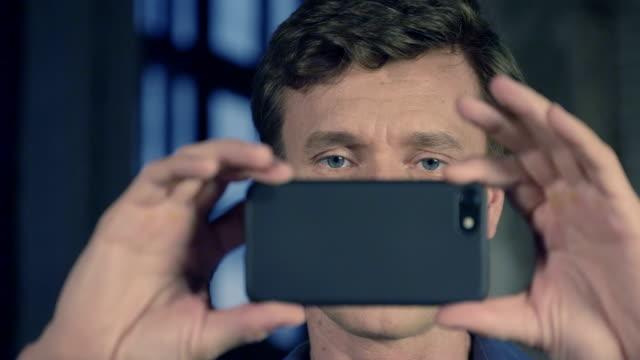 슬로우 모션 촬영 스튜디오에서 스마트폰 카메라를 사용 하 여 매력적인 남자의 초상화. 사업 시리즈입니다. - 영화 촬영 스톡 비디오 및 b-롤 화면