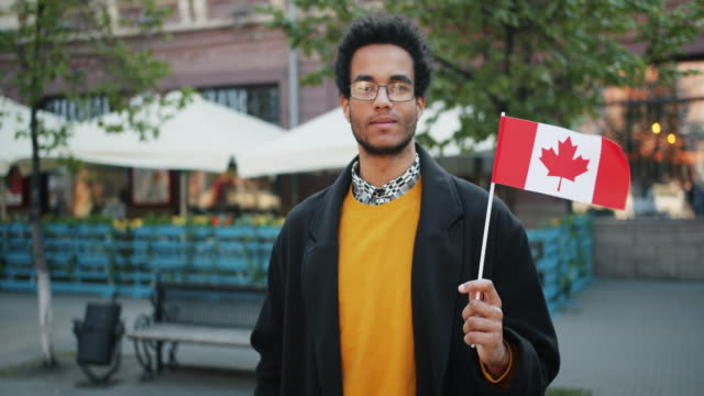 slow motion portrait of bearded african american man outdoors with canadian flag - canada flag stock videos & royalty-free footage