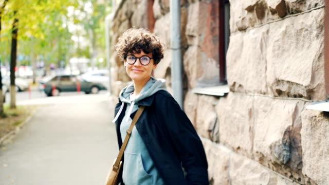 vídeos y material grabado en eventos de stock de cámara lenta retrato de hermosa niña slim caminando por la calle entonces girando, mirando a cámara y sonriendo. concepto de personas, el ocio y la ciudad joven. - moda de otoño