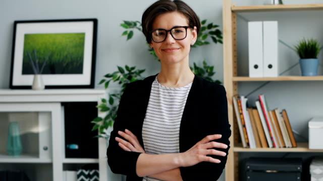 ritratto al rallentatore di imprenditrice che guarda la telecamera sorridere in ufficio - capelli castani video stock e b–roll