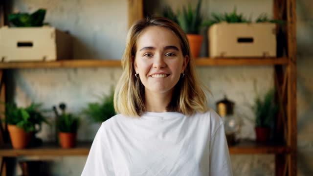 ağır çekim sarışın saç seyir kameraya, gülümseyerek ve ayakta kapalı modern dairede gülüyor neşeli kız portresi. genç insan ve olumlu duygular kavramı. - sarı saç stok videoları ve detay görüntü çekimi