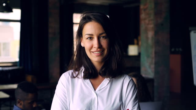 Slow motion portrait of cheerful young brunette office worker looking at camera and smiling while her multiracial team is working in background. People and work concept. Slow motion portrait of cheerful young brunette office worker looking at camera and smiling while her multiracial team is working in background. People, teams and work concept. adult stock videos & royalty-free footage