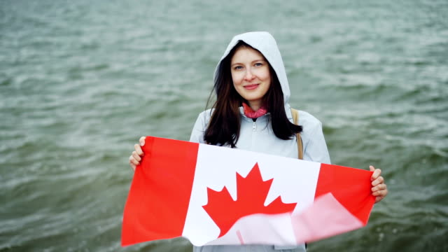 slow motion portrait of cheerful young lady proud citizen holding fluttering canadian flag and smiling looking at camera standing near the ocean. - canada flag stock videos & royalty-free footage
