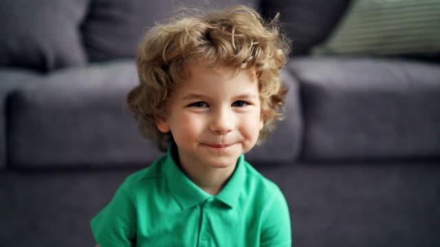 stockvideo's en b-roll-footage met slow motion portret van schattige kleine jongen kijken naar de camera en glimlachend thuis - jongen