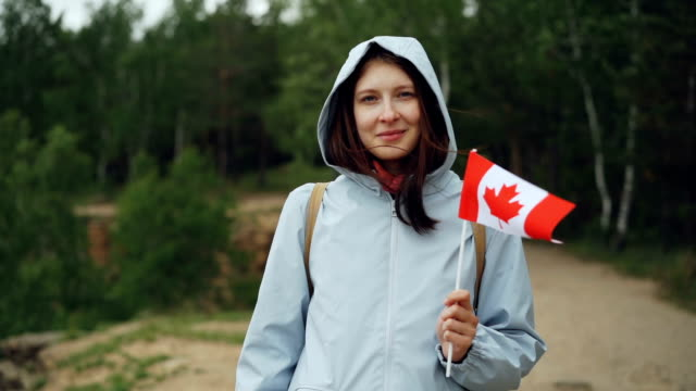 Slow motion portrait of female traveller pretty girl holding Canadian flag, smiling and looking at camera with beautiful natural landscape in background. video