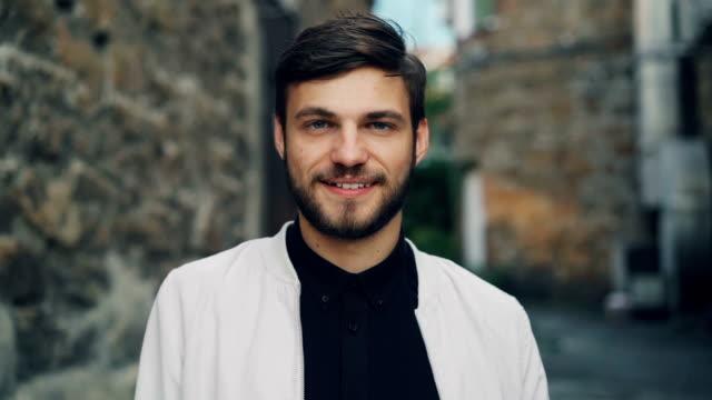 慢動作肖像的英俊鬍子的年輕男子穿著時髦的夾克和襯衫站在戶外與石牆在後臺, 微笑著, 看著相機。 - 高雅 個影片檔及 b 捲影像