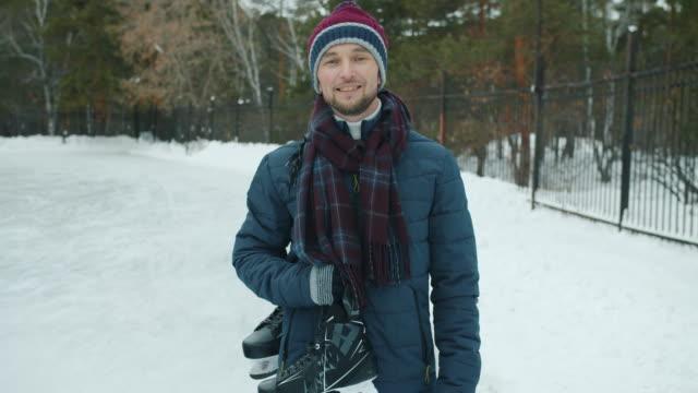 portret w zwolnionym tempie przystojnego faceta z łyżwami stojącymi na zewnątrz w parku uśmiechnięty - łyżwa filmów i materiałów b-roll