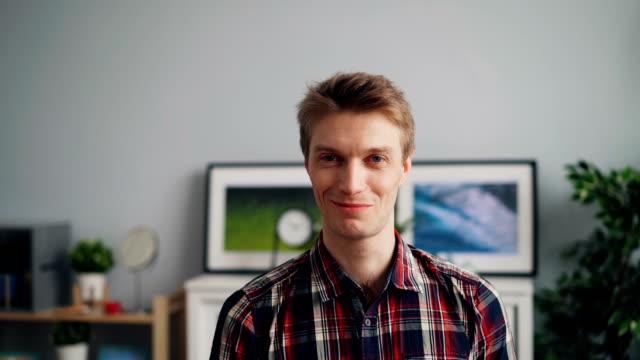 웃 고 집에 서 있는 카메라를 보고 잘생긴 남자의 슬로우 모션 초상화 - 이를 드러낸 미소 스톡 비디오 및 b-롤 화면