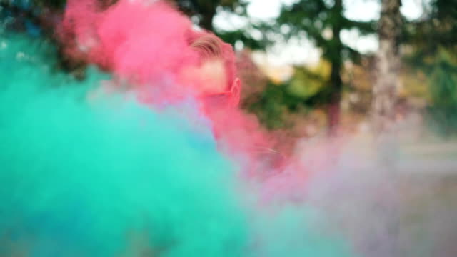 vídeos de stock e filmes b-roll de slow motion portrait of handsome man wearing bright sunglasses standing alone at holi festival with straight face then smiling and laughing when people are throwing paint at him. - holi